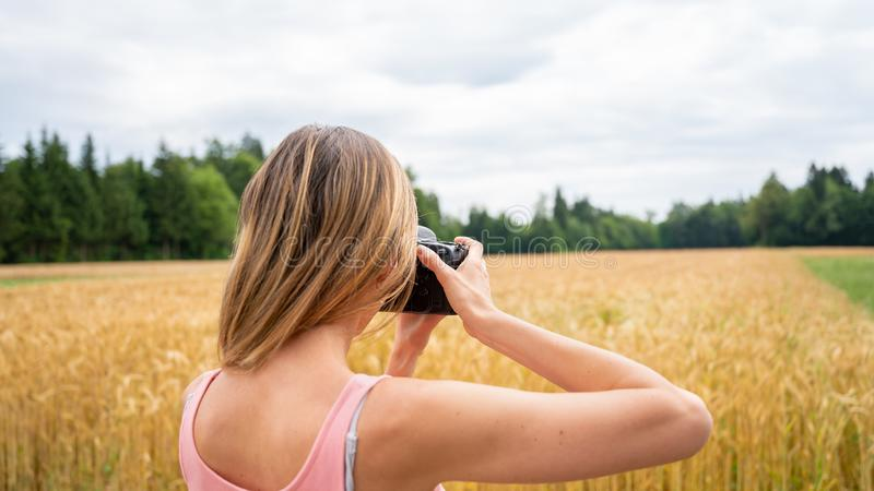 Weergeven van erachter van professionele vrouwelijke fotograaf die foto's in aard nemen royalty-vrije stock afbeelding