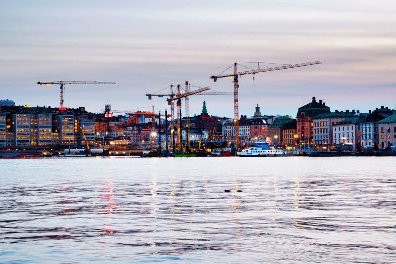 Weergeven van Gamla Stan in Stockholm, Zweden met bouwkranen tijdens de avond royalty-vrije stock afbeelding