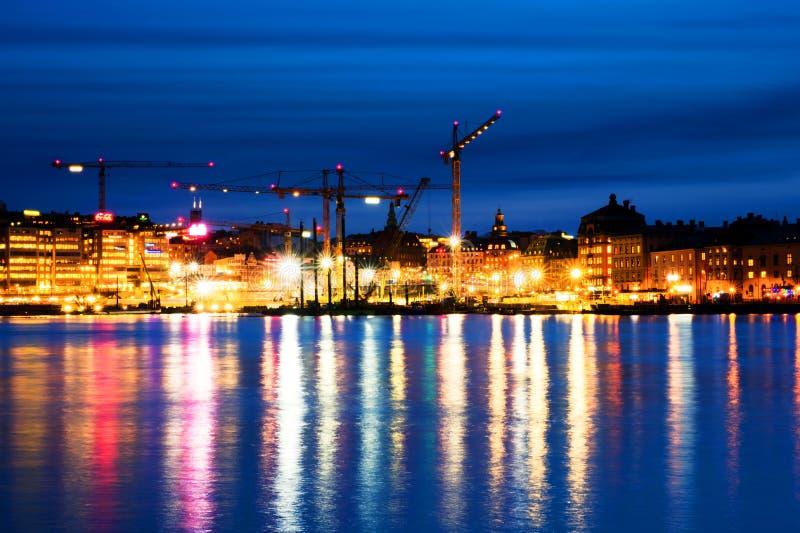 Weergeven van Gamla Stan in Stockholm, Zweden met bouwkranen tijdens de nacht stock afbeelding