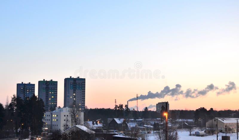 Weergeven van het avond stedelijke landschap, de hoge flatgebouwen en de rokende industriële pijpen bij zonsondergang, stock fotografie