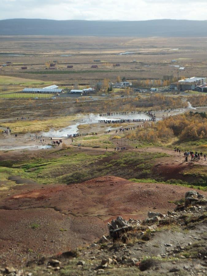 Weergeven van het geiser geothermische gebied in Haukadalur-Vallei, IJsland, met kleine cijfers van mensen die de uitbarsting bij stock foto's
