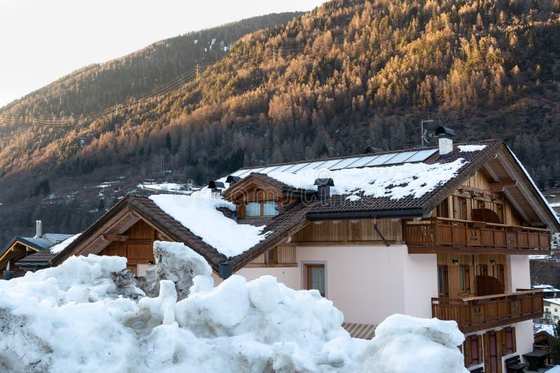 Weergeven van het huis achter een reusachtige sneeuwbank tegen de achtergrond van de bergen in Europa stock afbeelding