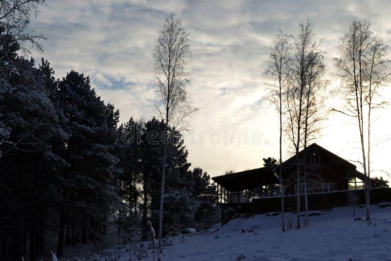 Weergeven van het huis op een heuvel onder het sneeuwbos in de stralen van de het plaatsen zon in de winter stock foto's