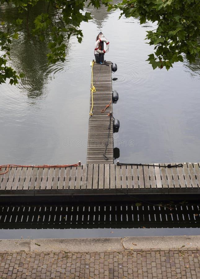 Weergeven van het kanaal, de pijler en het platform met reddingsboei in de stad van Vlaardingen stock foto