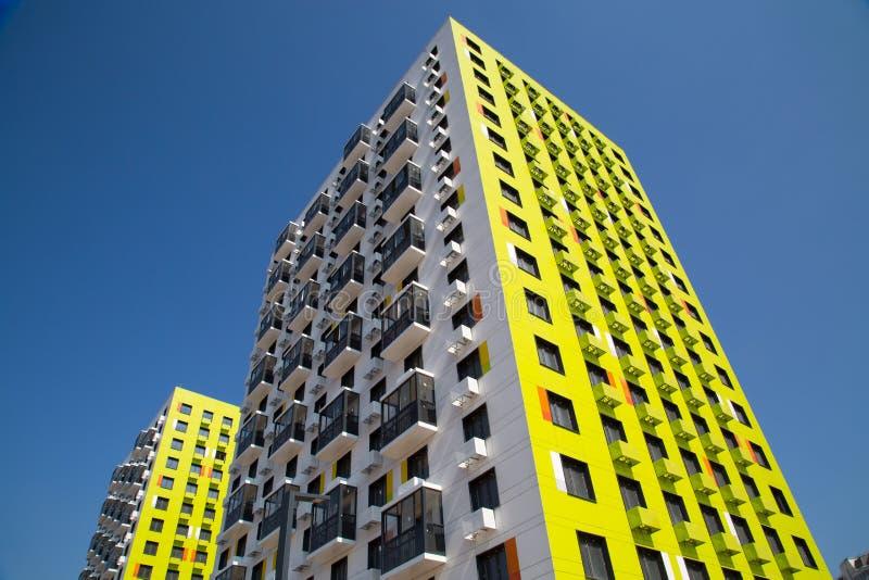 Weergeven van het nieuwe mooie flatgebouw van geelgroene kleur met oranje tussenvoegsels, scharnierende verglaasde balkons stock fotografie