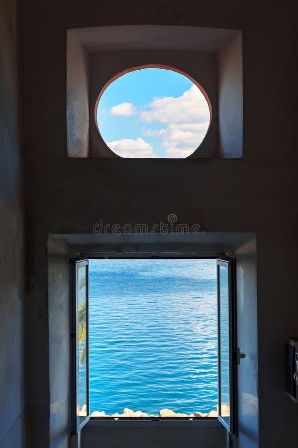 Weergeven van het overzees en de hemel door het venster Porto Santo Stefano in Monte Argentario Italië stock afbeelding