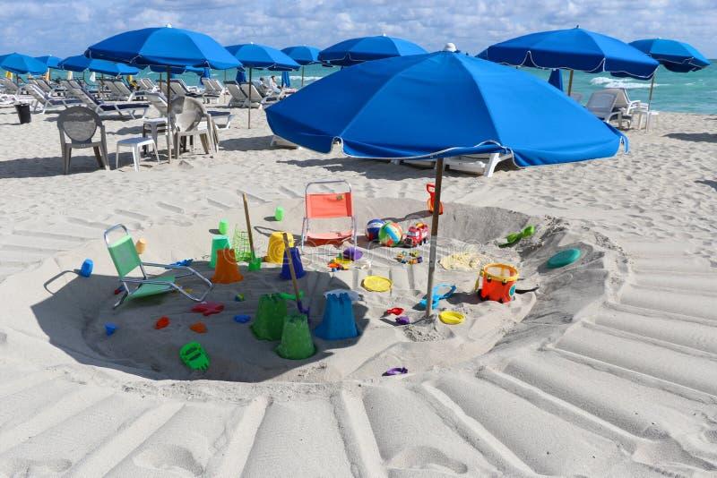 Weergeven van het strand van Miami met speelgoed en blueumbrellas stock fotografie