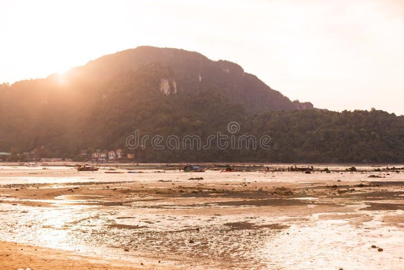 Weergeven van het strand op een groen tropisch eiland at low tide bij zonsondergang royalty-vrije stock fotografie