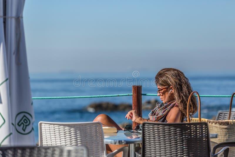 Weergeven van het technologische hogere vrouw nemen sunbath op strandclub, overzees als achtergrond, in Portugal stock foto's
