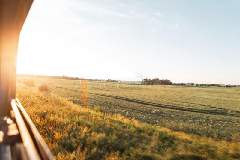 Weergeven van het treinvenster in de motie van het platteland en de blauwe hemel op een heldere zonnige warme de zomerdag bij zon royalty-vrije stock fotografie