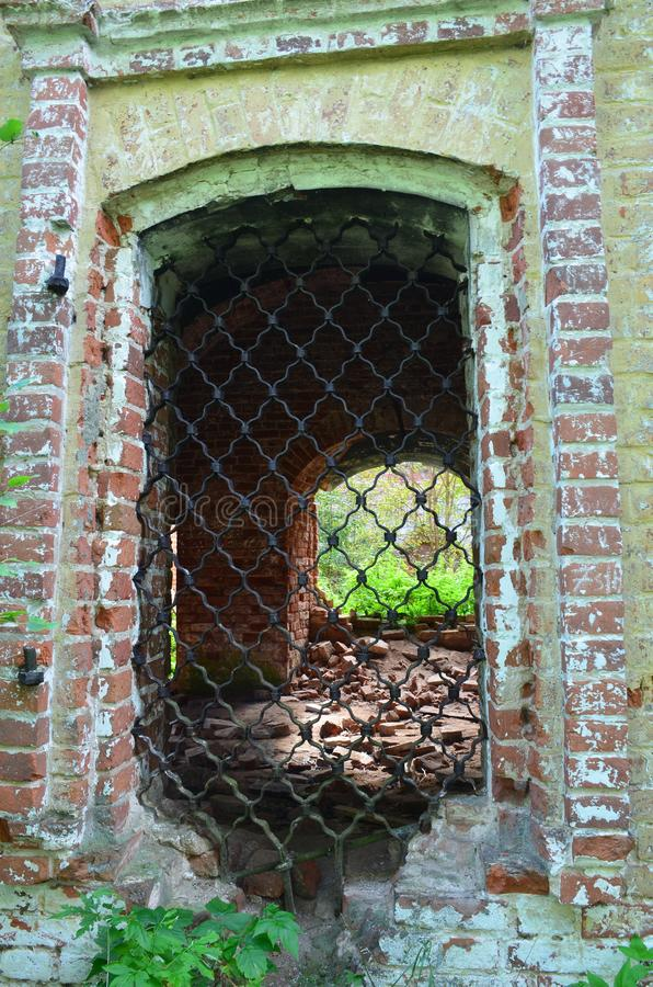 Weergeven van het venster met zwarte krullende gietijzergrating op de muur van oude vesting stock foto