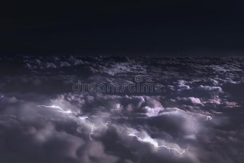 Weergeven van het venster van het vliegtuig aan de wolken bij nacht en bliksemflitsen stock afbeeldingen