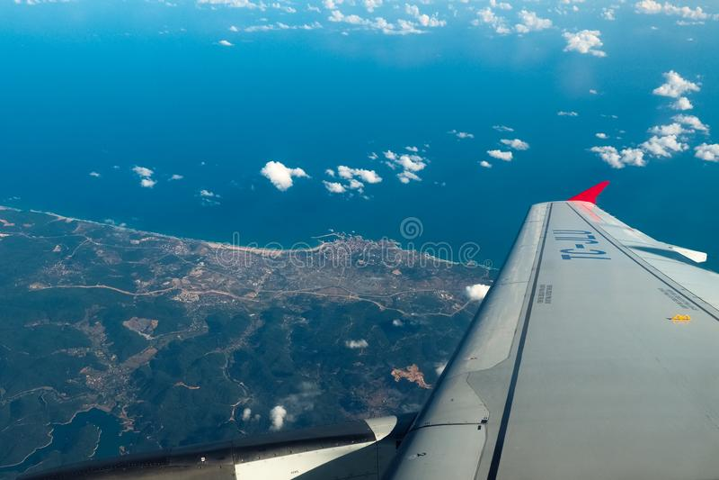 Weergeven van het venster van het vliegtuig op de vleugel, de aarde en de oceaan royalty-vrije stock foto