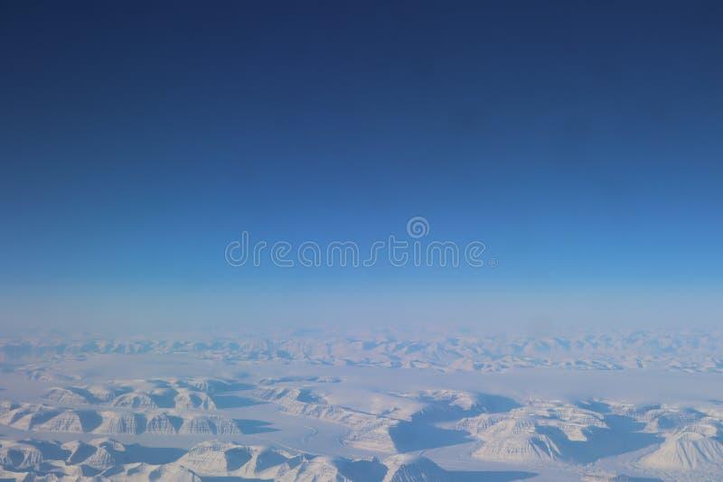 Weergeven van het vliegtuig aan sneeuwgroenland Landschap van sneeuwbergen van Groenland royalty-vrije stock fotografie