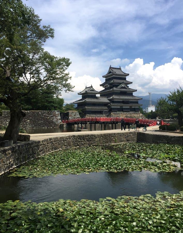 Weergeven van het zwarte houten Kasteel van Matsumoto in Japan stock foto's
