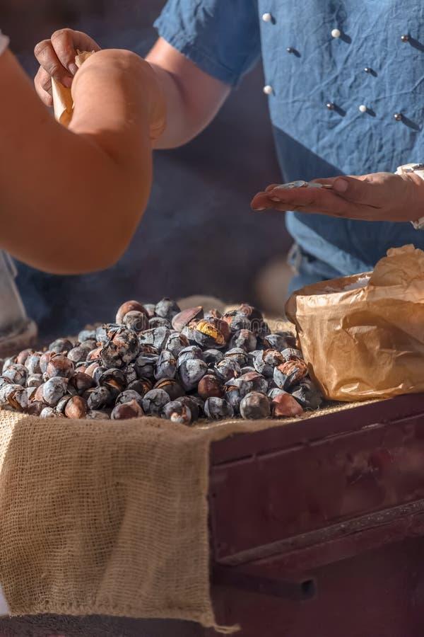 Weergeven van kastanjes in steenkool, op verkoop tegenbovenkant die worden geroosterd stock afbeeldingen