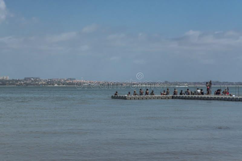 Weergeven van klein dok met mensen over, overzees en straalboot, op de kust van Mussulo-eiland, in Luanda, Angola royalty-vrije stock fotografie