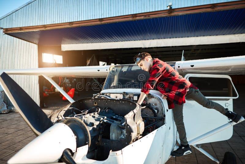 Weergeven van licht propellervliegtuig met geopend motorkabinet, tienerjongen die zich dichtbij bevinden stock fotografie