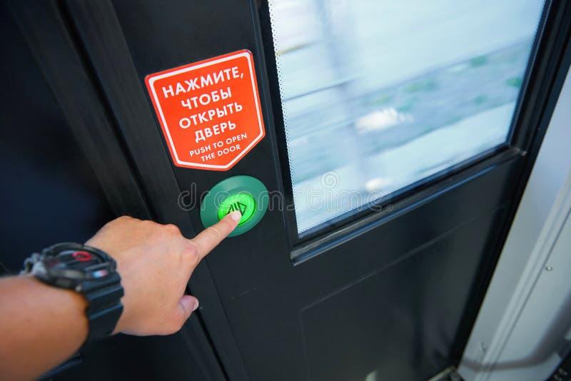 Weergeven van mensenhand die de deurdrukknop duwen maken signaal voor lokale deuren openen die terwijl treineinden bij een post o royalty-vrije stock fotografie