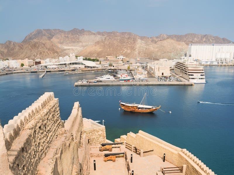Weergeven van Mutrah-Fort op de ingang aan de Mutrah-haven in Muscateldruif met een traditionele Omani boot Dhow en op de achterg royalty-vrije stock foto's