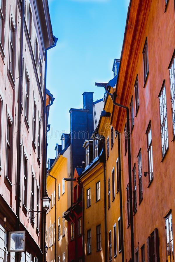 Weergeven van onderaan op comfortabele smalle middeleeuwse straat met verbonden geeloranje rode gebouwenvoorgevels in stan Gamla, stock foto