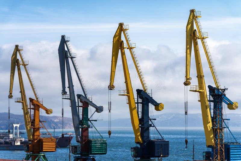 Weergeven van oude havenkranen in zeehaven op kust van oceaan stock afbeelding