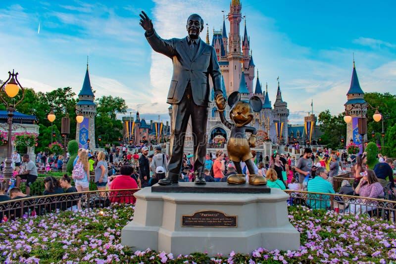 Weergeven van Partners Walt Disney en Mickey Mouse-standbeelden en kleurrijke bloemen bij Magisch Koninkrijk in Walt Disney World stock foto's