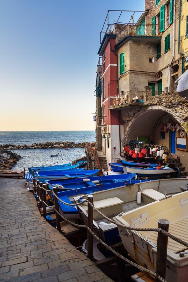 Weergeven van smalle straat met boten en overzees in Riomaggiore, Cinque Terre Italië stock afbeelding