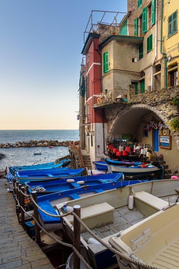 Weergeven van smalle straat met boten en overzees in Riomaggiore, Cinque Terre Italië stock afbeeldingen