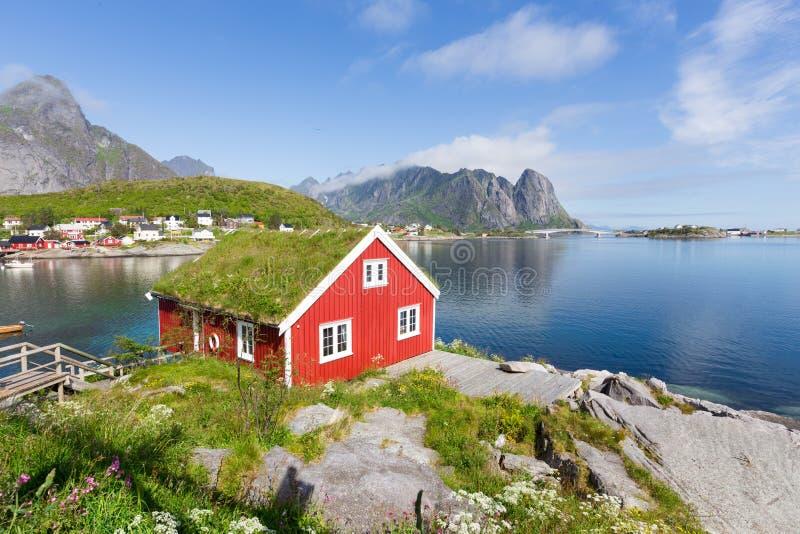 Weergeven van traditionele Noorse rode hut in Lofoten-eilanden Mooie de zomerdag en blauwe hemel stock fotografie