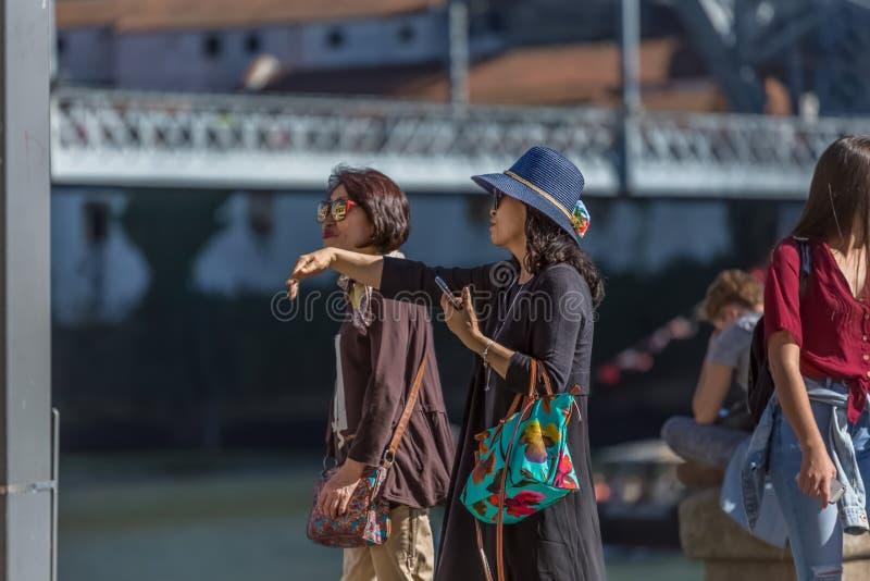 Weergeven van twee Aziatische hogere vrouwen die binnen de stad in van Porto stad, brug en rivier als achtergrond lopen royalty-vrije stock foto
