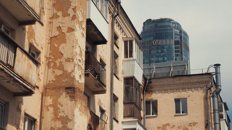 Weergeven van vijf-verhaal baksteen woonhuis tegen de achtergrond van moderne glaswolkenkrabber in Ekaterinburg voorraad stock afbeeldingen