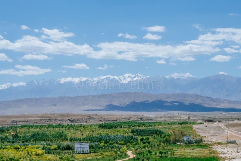 Weergeven van vlakte onder bergen en hemel bij Jiayu-Pas, in Jiayugua stock afbeelding
