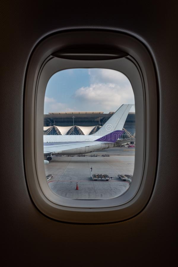 Weergeven van vliegtuigvenster van de vliegtuigstaart in luchthaven en blauwe hemel wordt geparkeerd die royalty-vrije stock afbeeldingen