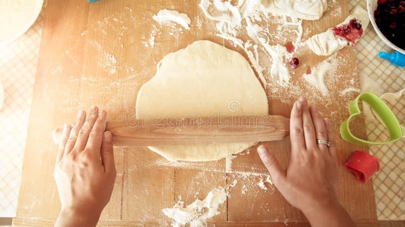Weergeven vanaf de bovenkant op jonge vrouw die deeg maken en het rollen met houten deegrol op keuken counterboard stock afbeeldingen