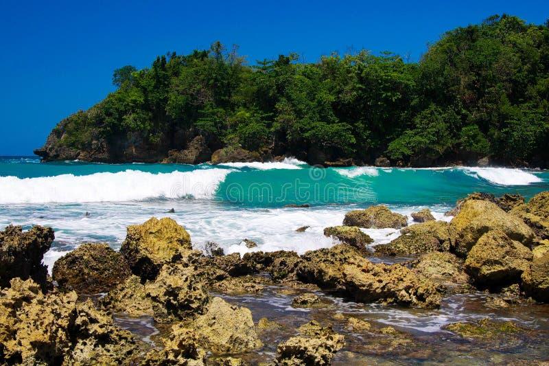 Weergeven voorbij scherpe rotsen op turkooise ruwe overzees met golfbrekers en sterke branding - Blauwe lagune, Portland, Jamaïca stock fotografie