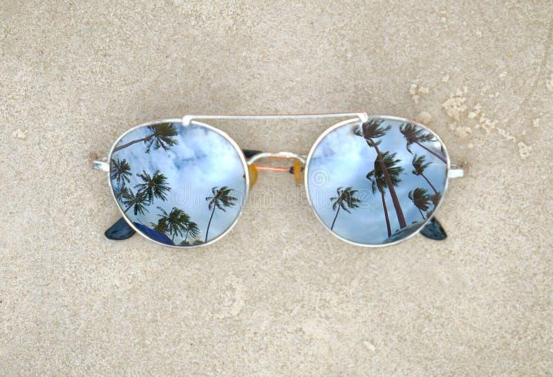 Weerspiegelde zonnebril dicht omhoog op het strandzand met palmenbezinning stock foto's