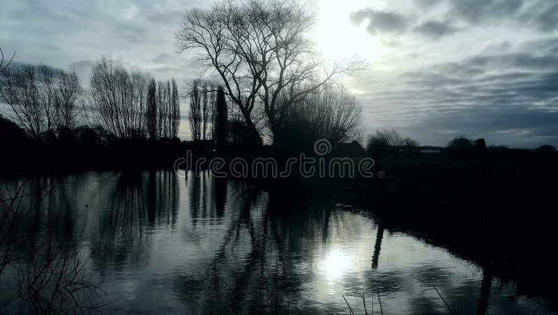 Weerspiegelend zonlicht in grote vijver tijdens de winterzonsondergang royalty-vrije stock afbeeldingen