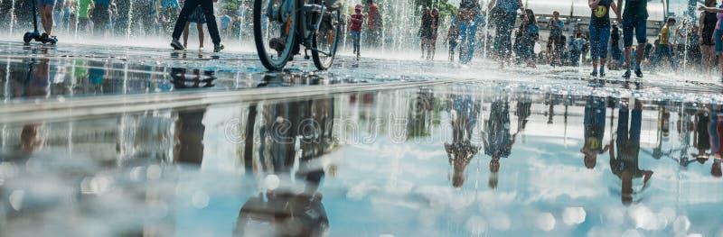 Weerspiegeling van de menigte van vrolijke mensen in de stadsfontein, in de pool Heldere zonnige de lente of de zomerdag stock fotografie