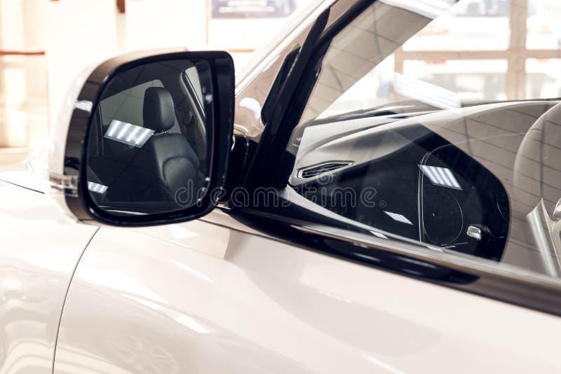 Weerspiegeling van het binnenland van een moderne witte auto in de zijspiegel stock foto