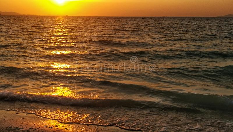 Weerspiegeling van schemering over kleine golven die aan het strand aanvallen royalty-vrije stock fotografie