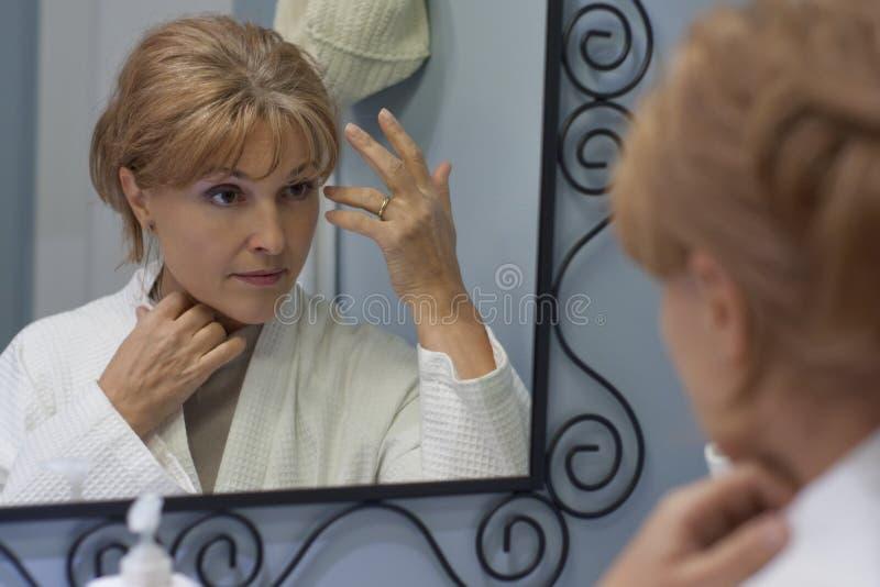 Weerspiegeling van vrouw het kijken in spiegel stock afbeeldingen