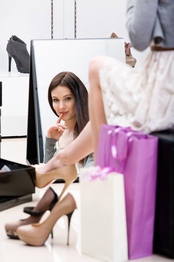 Weerspiegeling van vrouw het proberen op schoeisel stock foto