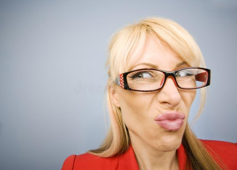 Weerzinwekkende vrouw in rood dat een grappig gezicht maakt stock fotografie