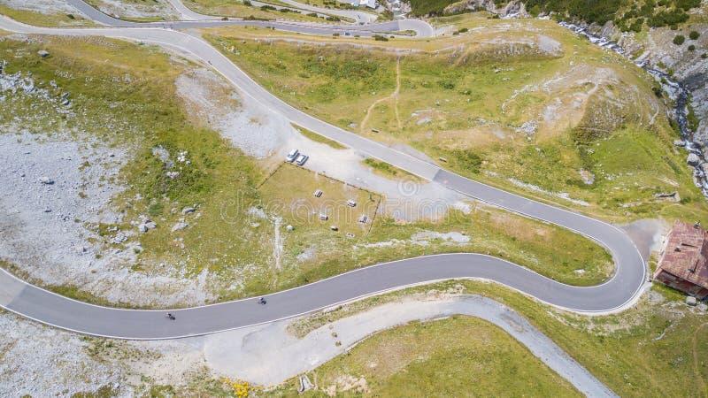 Weg aan de Stelvio-bergpas in Italië Boven en beneden verbazende luchtmening van de bergkrommingen die tot mooie vormen leiden royalty-vrije stock foto