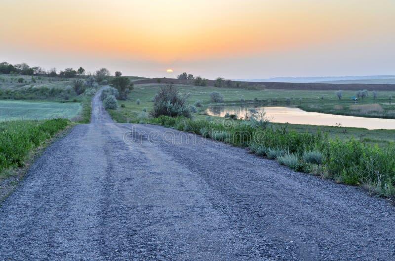 Weg aan horizon in zonsondergang Zonsondergang in diepe blauwe hemel over asfaltweg De achtergrond van de reis royalty-vrije stock foto