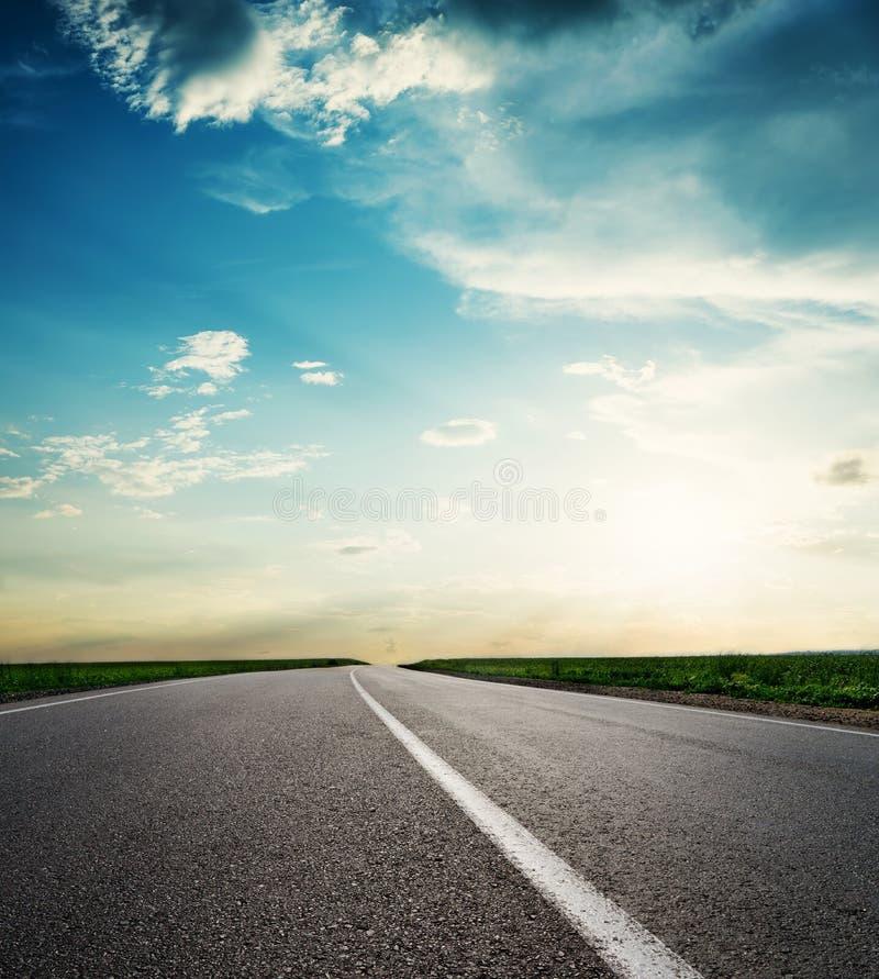 Weg aan horizon in zonsondergang Lage wolken met zon over asfalt stock fotografie