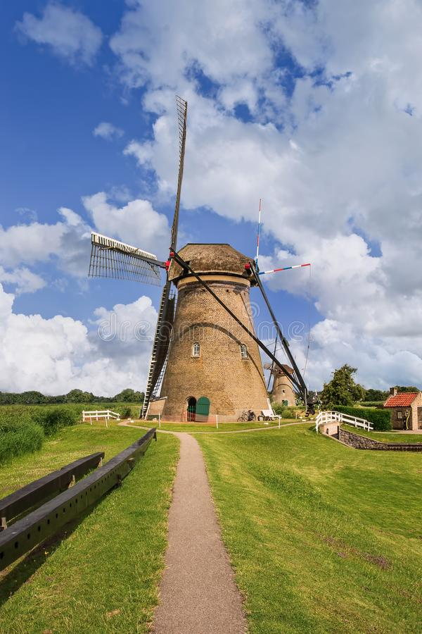 Weg aan oude windmolen op een de zomerdag in beroemde Kinderdijk, Nederland stock foto's