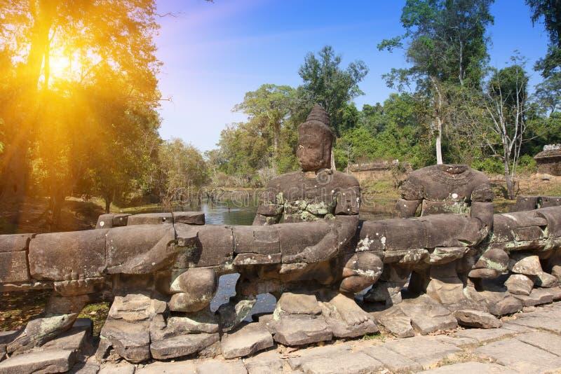Weg aan tempel, hout en rivier, ruïnes van standbeelden, 12de eeuw, Kambodja stock afbeelding