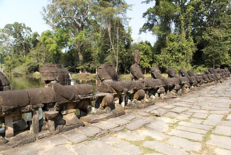 Weg aan tempel, hout en rivier, ruïnes van standbeelden, 12de eeuw, Kambodja royalty-vrije stock foto's